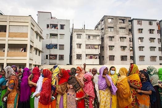 People wait for relief aid in Dhaka, Bangladesh, amid the coronavirus pandemic, disregarding social distance guidelines.