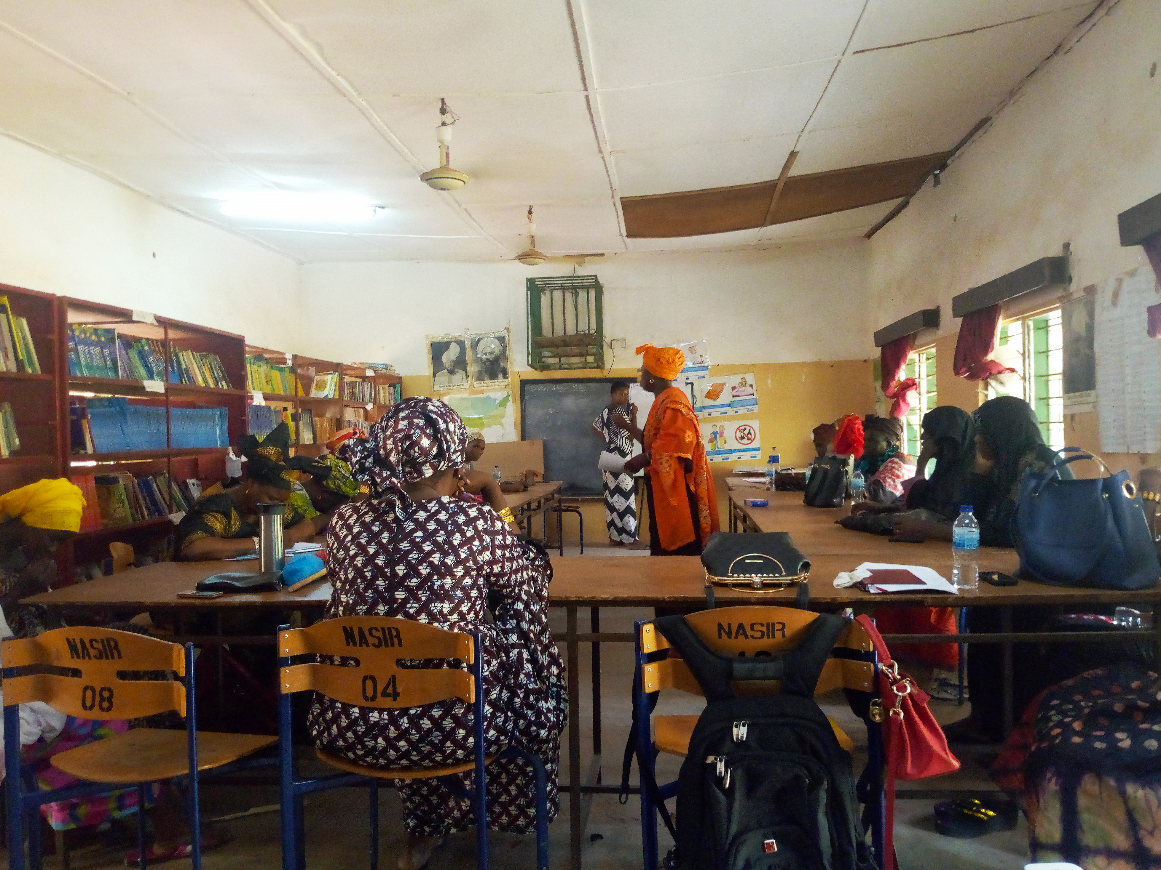 Women in The Gambia meeting in a classroom, sitting at school desks and writing on a black board.