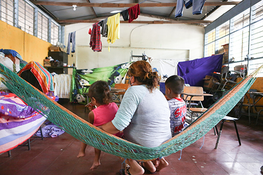 A woman and her children seek refuge in a temporary makeshift shelter in Honduras in November 2020 after hurricanes devastated the region.